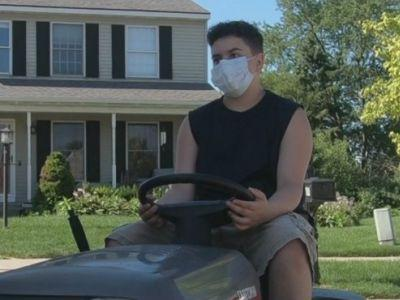 Business owner gives lawnmower to young entrepreneur