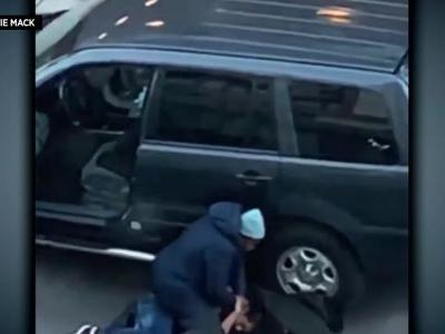 Mom caught on camera sitting on attempted car thief refusing to let him go