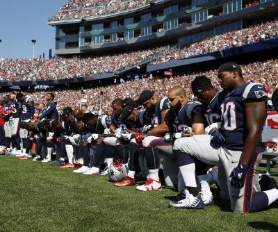 Dozens of Patriots kneel, others interlock arms during national anthem