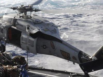 Helicopter crashes on the flight deck of a US Navy carrier, injuring sailors