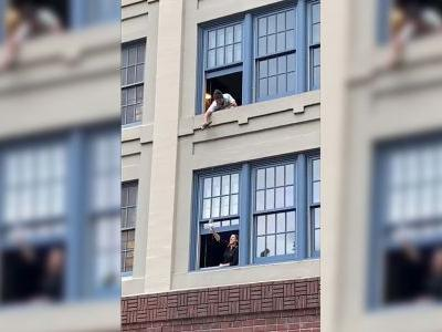 Two Neighbors Share Wine Out the Window While Supporting Healthcare Workers