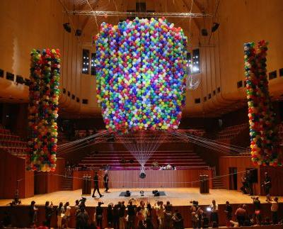 Artist gets lifted up by 20,000 party balloons inside the Sydney Opera House
