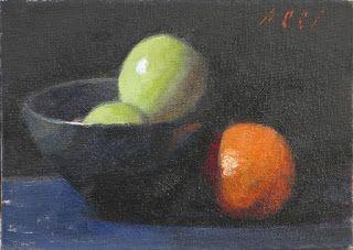 Black bowl with apples and orange