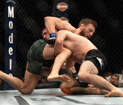 Conor McGregor taps to a tight Khabib Nurmagomedov neck crank, who jumps the cage and nearly incites a riot after his victory