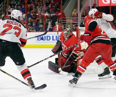 Canes beat Devils 3-1, clinch 1st playoff berth since '09