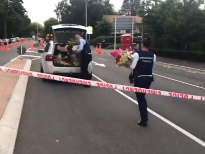 Video shows New Zealand police carrying heaps of flowers past cordon to lay at mosque where gunman killed 41