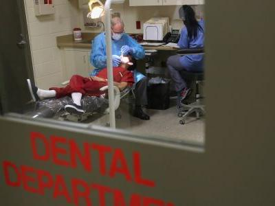 A dentist at an immigration detention facility told inspectors he doesn't have time for cleanings or fillings - but suggested immigrants floss with string from their socks if they're 'dedicated to dental hygiene'