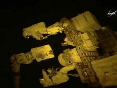Spacewalking astronauts give a hand to robot arm