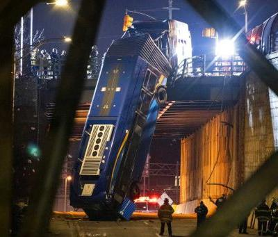 Photos: New York City bus left dangling from overpass after crash