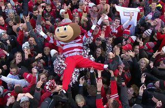 Brutus the Buckeye crowd surfs as Ohio State fans rush the field after win vs. Michigan