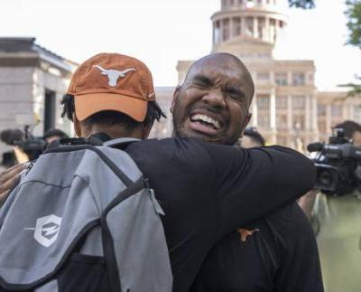 Texas Longhorns football players and staff walk to state capitol for emotional rally