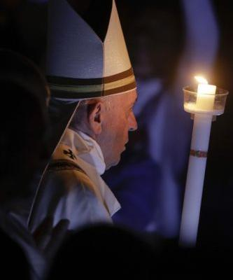Pope carries Easter candle up aisle of darkened basilica